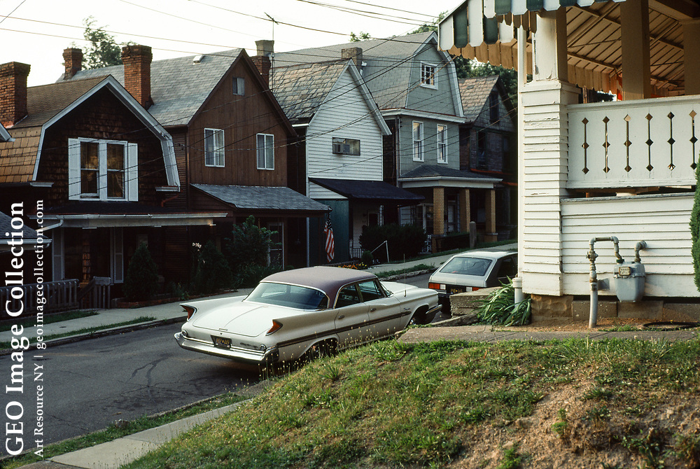 Modest rowhouse bungalow houses with a circa 1960 car with tail fin is a Chrysler sedan automobile with tailfins introduced in the 1950's.  The houses on Edith Street are in the residential Duquesne Heights neighborhood and home to many working class families.