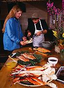 Chef Steve Lacroix serving salmon to Amanda Brannon, Winterlake Lodge seafood dinner, Alaska.