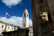 Stone gargoyle, town clock tower and Croatian flag. Dubrovnik old town, Croatia