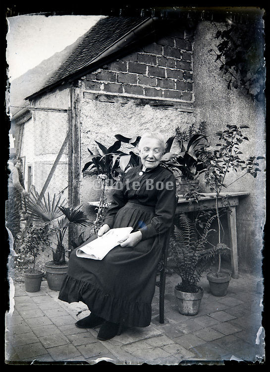 content senior woman sitting in little yard by the house France circa 1930s