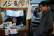 A tiny stall. Dealers aren't allowed to touch money so each stall has its own cashier. Tsukiji market in Tokyo. Japan 2013