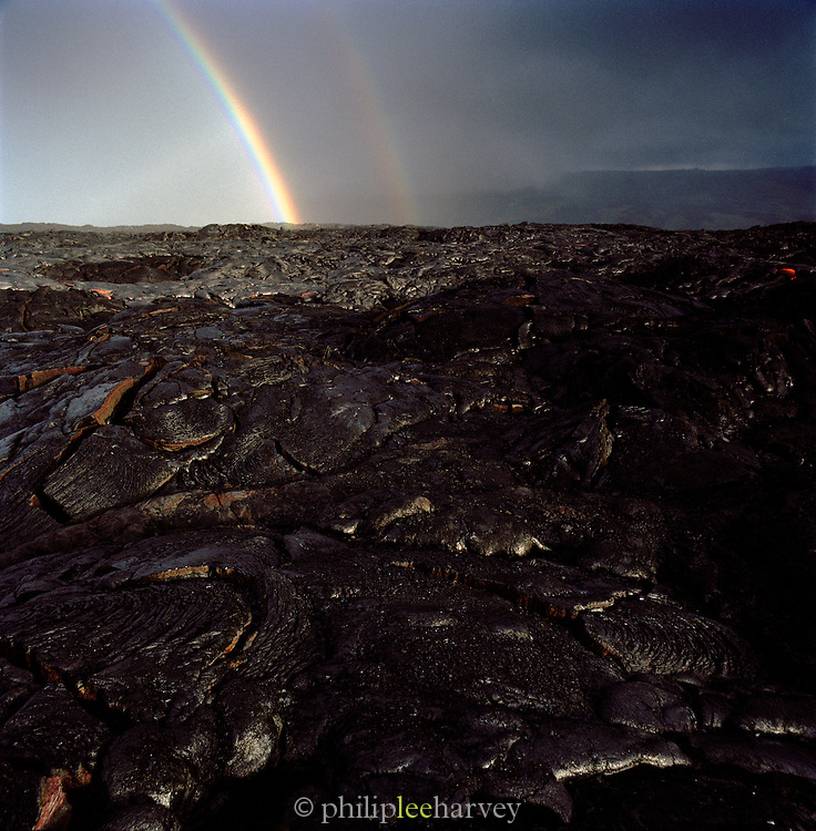 A rainbow strikes cooled lava rock, Hawaii Volcanoes National Park, Hawaii, USA