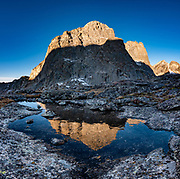 """Near Jackass Pass, War Bonnet Peak catches sunrise light, in Cirque of the Towers, Bridger Wilderness, Wind River Range, Bridger-Teton National Forest, Rocky Mountains, Wyoming, USA. We backpacked to Big Sandy Lake Campground (11 miles round trip with 1000 feet gain). Two hours before sunrise, I departed from Big Sandy Lake to reach Jackass Pass viewpoint for Cirque of the Towers and Lonesome Lake (6.5 miles round trip, 1860 ft gain) on the Continental Divide Trail. The Continental Divide follows the crest of the """"Winds"""". Mostly composed of granite batholiths formed deep within the earth over 1 billion years ago, the Wind River Range is one of the oldest mountain ranges in North America. These granite monoliths were uplifted, exposed by erosion, then carved by glaciers 500,000 years ago to form cirques and U-shaped valleys. This image was stitched from multiple overlapping photos."""