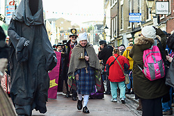 "© Licensed to London News Pictures. 08/12/2019. ROCHESTER, UK. A man dressed as Scrooge, accompanied by a man dressed as Death, both from ""A Christmas Carol"", take part in the annual Dickensian Christmas Festival in Rochester.  The Kent town is given a Victorian makeover to celebrate the life of the writer Charles Dickens (who spent much of his life there), with Victorian themed street entertainment, costumed parades and a Christmas market.  Photo credit: Stephen Chung/LNP"