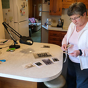 Denise Wolfe arranges pictures of her dad, Ken Snyder, at his Dorian Drive home in Maumee, Ohio, on Saturday, Feb. 22, 2020. Brothers George Snyder, Jr., 97, and Ken Snyder, 96, both served in World War II. THE BLADE/KURT STEISS <br /> MAG WWIIVet01