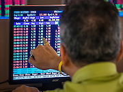 08 JULY 2015 - BANGKOK, THAILAND: A man monitors stocks he is interested in at a public computer terminal in a Bangkok brokerage house. Thai financial markets and the Thai Baht both lost value Wednesday. The stock market, the Stock Exchange of  Thailand (SET) closed at 1,470.25, down 13.52 or 0.91%, from Tuesday. The Thai Baht closed at 33.90 Baht to 1 US Dollar, it's lowest point since September 2009. Economists blamed the drop in the Chinese stock markets and uncertainty over the EU's handling of the Greek budget crisis for the drops in Thai markets.     PHOTO BY JACK KURTZ