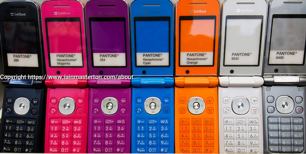 Row of colourful modern mobile phone handsets in a Tokyo shop in Japan