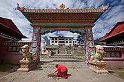 A monk repairs paving outside a monastery set in the Himalayas, Nepal. Image by Greg Beadle