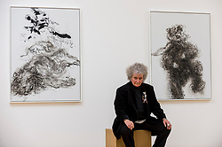 """© Licensed to London News Pictures. 14/10/2020. LONDON, UK. Artist Maggi Hambling poses with her works """"Lion in enclosure"""", 2019 (L) and """"Young dancing bear"""", 2019, at the preview of Maggi Hambling: 2020 at Malborough Gallery in Mayfair.  The exhibition of recent paintings coincides with Hambling's 75th Birthday and runs 15 October to 21 November 2020.  Photo credit: Stephen Chung/LNP"""