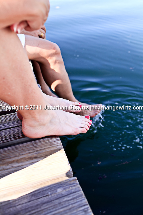 The bare legs and feet of three people sitting on a dock. WATERMARKS WILL NOT APPEAR ON PRINTS OR LICENSED IMAGES.