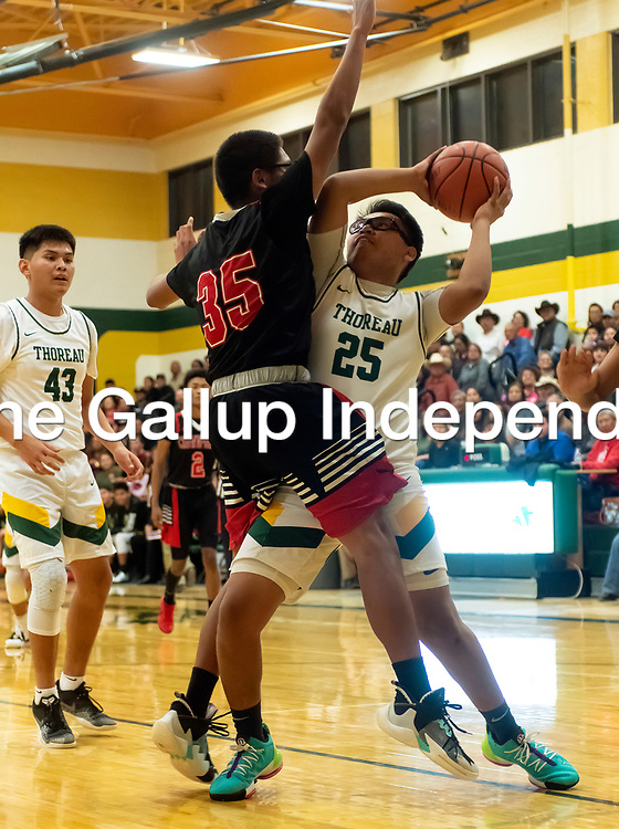 Photo - Jeffery Jones<br /> <br /> Crownpoint Eagle Quincy Benally (35) stands in front of Thoreau Hawk Louie Delgarito (25) as he looks to make a basket during Friday night's game at Thoreau High School