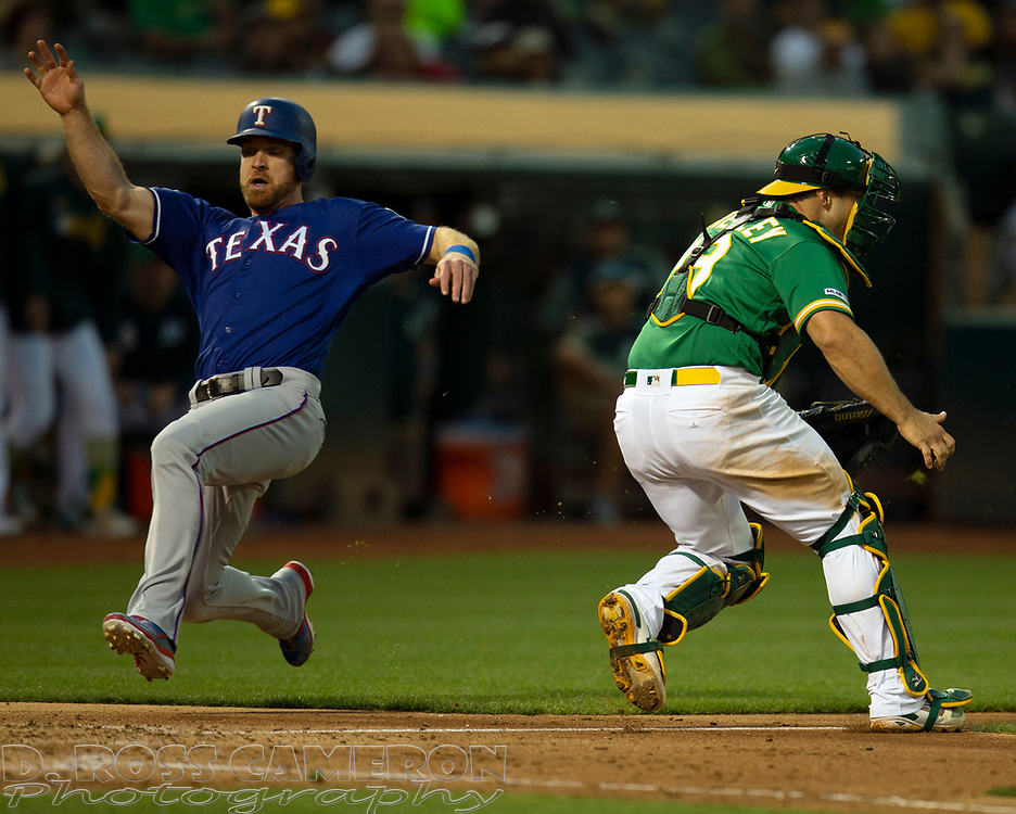 Jul 25, 2019; Oakland, CA, USA; Texas Rangers first baseman Logan Forsythe (41) slides safely home on a single by Delino DeShields while Oakland Athletics catcher Josh Phegley (19) waits on the late relay during the fifth inning of a baseball game at Oakland Coliseum. Mandatory Credit: D. Ross Cameron-USA TODAY Sports