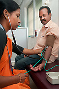 India. Orissa. Sambalpur. September 2012. Dr Shiva's downtown eye clinic. An ophthalmic assistant takes blood pressure.