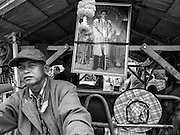 21 FEBRUARY 2014 - KHLONG CHIK, PHRA NAKHON SI AYUTTHAYA, THAILAND: A Thai farmer in front of a portrait of Bhumibol Adulyadej, the King of Thailand, on the highway south of Ayutthaya. About 10,000 Thai rice farmers, traveling in nearly 1,000 tractors and farm vehicles, blocked Highway 32 near Bang Pa In in Phra Nakhon Si Ayutthaya province. The farmers were traveling to the airport in Bangkok to protest against the government because they haven't been paid for rice the government bought from them last year. The farmers turned around and went home after they met with government officials who promised to pay the farmers next week. This is the latest blow to the government of Yingluck Shinawatra which is confronting protests led by anti-government groups, legal challenges from the anti-corruption commission and expanding protests from farmers who haven't been paid for rice the government bought.    PHOTO BY JACK KURTZ