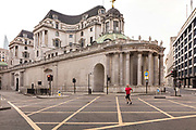 Man jogging in the deserted street behind the Bank of England during the coronavirus pandemic on the 10th May 2020 in London, United Kingdom.