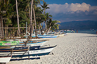 Palm trees and traditional fishing boats on beautiful White Sand beach, Boracay, Philippines.