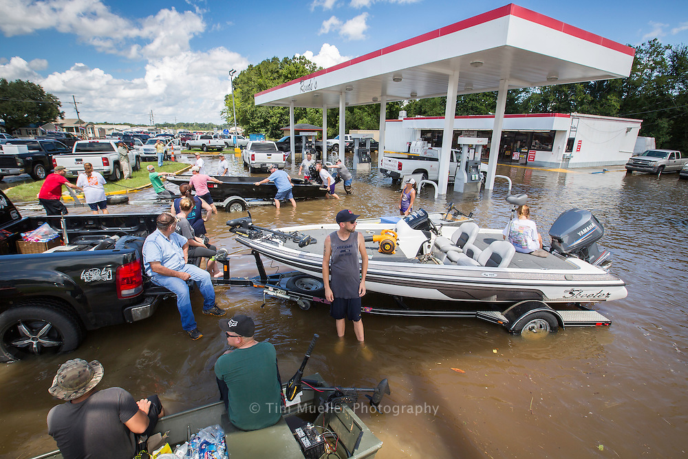 The water-filled Rendi's gas station at Airline Highway and Hwy. 431 serves as a rendezvous point for St. Amant residents fleeing area flooding Tuesday, August 16, 2016.