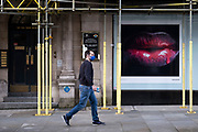 Man wearing a face mask passes pictures of glistening lips with red dripping lipstick on Bond Street which has all shops closed as the national coronavirus lockdown three continues on 28th January 2021 in London, United Kingdom. Following the surge in cases over the Winter including a new UK variant of Covid-19, this nationwide lockdown advises all citizens to follow the message to stay at home, protect the NHS and save lives. Bond Street is one of the principal streets in the West End shopping district and is very upmarket. It has been a fashionable shopping street since the 18th century. The rich and wealthy shop here mostly for high end fashion and jewellery.