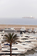 Luxury yachts moored inside a marina wall while outside a container ships sails on the Mediterranean Sea at Beirut, Lebanon