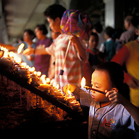 Philippines, Cebu Island, Boy lights devotional candles at Basilica del Santo Niño in Cebu City
