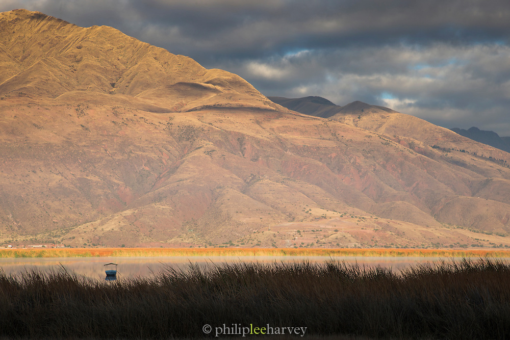 Boat on the water at sunrise in the Huacarpay Valley, Sacred Valley, Peru, South America