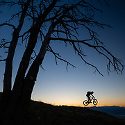 Andrew Whiteford gets some air along a ridge on Teton Pass heading towards Black's Canyon at sunrise near Wilson, Wyoming.
