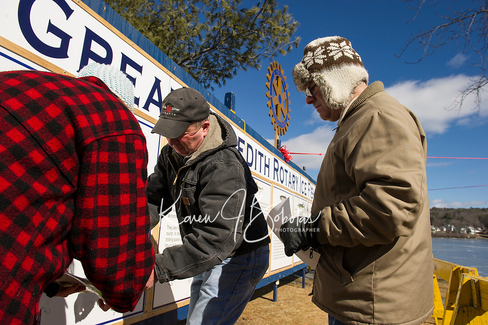 """Betsy Moulton Donovan, John Moulton and Ted Fodero prepare the """"Wall"""" for this weekend's annual Great Meredith Rotary Ice Fishing Derby.  (Karen Bobotas/for the Laconia Daily Sun)"""