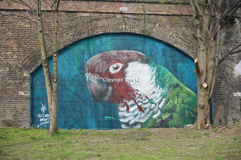 London,England,UK : 11th April 2016 : 'Endangered 13' Project street artists painting a 'Parrot' raising awareness Endangered animal at Ackroyd Drive, Sponsor by Tower Hamlets council in London. Photo by See Li