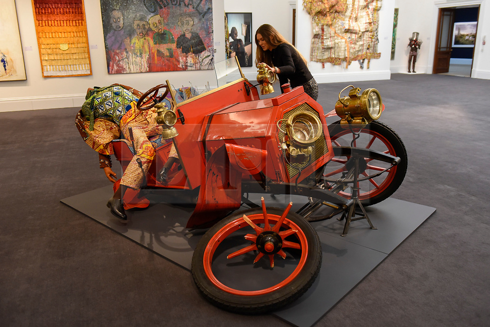 """© Licensed to London News Pictures. 12/05/2017. London, UK.   A staff member views """"Crash Willy"""", 2009, by Yinka Shonibare (Britain-Nigeria) (Est. GBP 120-180k) at the preview for the first sale dedicated to Modern and Contemporary African Art at Sotheby's New Bond Street.  The sale features over 115 artworks by over 60 different artists from 14 countries across the continent. Photo credit : Stephen Chung/LNP"""