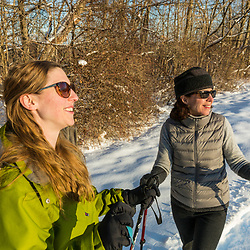 Two women snowshoeing in a field on Indian Hill in West Newbury, Massachusetts.