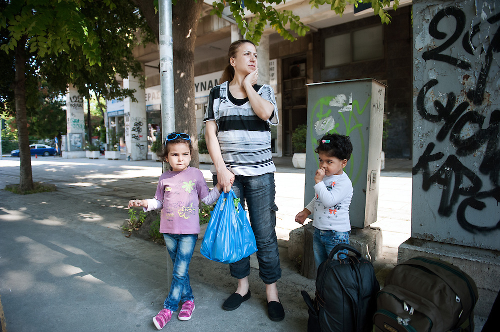 Morning of Sunday 13 September 2015. Aysha and her two daughters Sham (L) and Bisan (R) waiting in Egnantia street in Thessaloniki for the city bus to take them to the central bus station in order to take another bus to Idomeni on the Greek - Macedonian border. They arrived to the port of Kavala in mainland Greece last night, where they took a bus to Thessaloniki. All of the other refugees and immigrants continued their journey last night to the border, but Aysha was tired and with a swollen ankle she preferred to spend a night in a hotel.