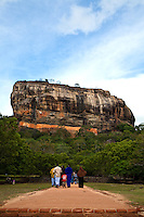 Sigiriya, or Lion's rock, is an ancient rock fortress and palace ruin surrounded by the remains of an extensive network of gardens, reservoirs, and other structures. A popular tourist destination, Sigiriya is also renowned for its ancient fresco paintings which are reminiscent of the Ajanta Caves of India.  Sigiriya was built during the reign of King Kassapa I and it is one of the seven World Heritage Sites of Sri Lanka.  The Sigiriya rock is a hardened magma plug from an extinct and long-eroded volcano. It stands high above the surrounding plain, visible for miles in all directions. The rock rests on a steep mound that rises abruptly from the flat plain surrounding it. The rock itself rises 370m (1,214 ft) above sea level and is sheer on all sides, in many places overhanging the base. It is elliptical in plan and has a flat top that slopes gradually along the long axis of the ellipse.