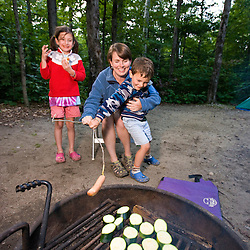 A woman and her kids cook over the fire while camping  in Crawford Notch State Park in New Hampshire's White Mountains.