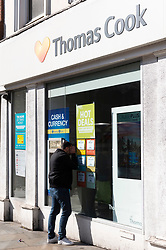 © Licensed to London News Pictures. 23/09/2019. London, UK. A man looks through the window of a closed Thomas Cook holiday store in North London. British holiday package firm Thomas Cook announced it is in administration.The company failed to raise an additional £200 million of funds to secure a rescue package was not forthcoming.Photo credit: Ray Tang/LNP