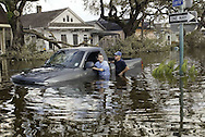 Two men push their truck in flooded New Orleans August 30, 2005. Floodwaters engulfed much of New Orleans on Tuesday as officials feared a steep death toll and planned to evacuate thousands remaining in shelters after the historic city's defenses were breached by Hurricane Katrina. REUTERS/Rick Wilking