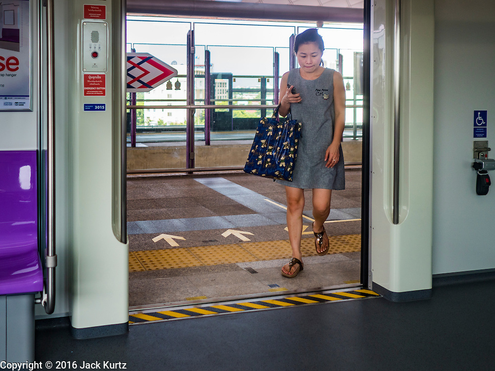 """23 AUGUST 2016 - NONTHABURI, NONTHABURI, THAILAND:  A passenger boards a """"Purple Line"""" train, the new Bangkok commuter rail line that runs from Bang Sue, in Bangkok, to Nonthaburi, a large Bangkok suburb. The Purple Line is run by the  Metropolitan Rapid Transit (MRT) which operates Bangkok's subway system. The Purple Line is the fifth light rail mass transit line in Bangkok and is 23 kilometers long. The Purple Line opened on August 6 and so far ridership is below expectations. Only about 20,000 people a day are using the line; officials had estimated as many 70,000 people per day would use the line. The Purple Line was supposed to connect to the MRT's Blue Line, which goes into central Bangkok, but the line was opened before the connection was completed so commuters have to take a shuttle bus or taxi to the Blue Line station. The Thai government has ordered transit officials to come up with plans to increase ridership. Officials are looking at lowering fares and / or improving the connections between the two light rail lines.    PHOTO BY JACK KURTZ"""