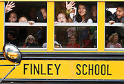 Finley Elementary School students wave goodbye to faculty and staff on June 7, 2012 before the annual bus parade on the last day of school in Finley School District.