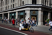Cycle taxi passes the famous jewellers Mappn & Webb on Regent Street in the West End of London