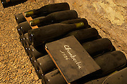 In the underground wine cellar: a pile of bottles of Chambertin Grand Cru 1996 red Burgundy wine with the appellation written in white text on a black chalkboard chalk board on a gravelly pebbly soil, Maison Louis Jadot, Beaune Côte Cote d Or Bourgogne Burgundy Burgundian France French Europe European