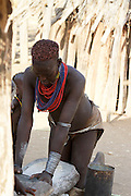 Africa, Ethiopia, Omo Valley, Woman of the Karo tribe grinding grain to four
