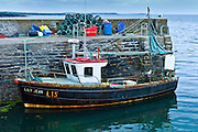 Fishing trawler boat by lobster pots at Slade Harbour, County Wexford, Southern Ireland