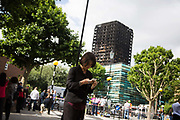 A tv presenter gets ready below the Grenfell Tower June 16th 2017, London, United Kingdom. Grenfell Tower burned out after a catastophic fire killing more than 58 people. The tower caught fire early Wednesday morning and final casualty figueres may end up to be many more with police not expecting to be able to find and recover all bodies and to find all missing people. No fire sprinkler in place and cheap cladding made with plastic is so far blamed for the ferocious fire.