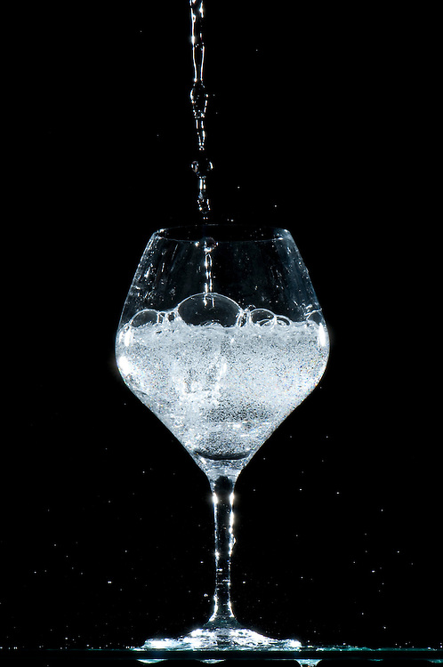 Close-up of sparkling water being poured into a glass.