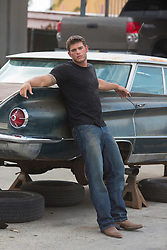 very good looking muscular auto mechanic with grease and dirt on his face leaning against a classic car in repair