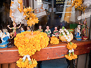 04 OCTOBER 2009 -- BANGKOK, THAILAND:  Buddhist offerings in front of a bar in the Patpong section of Bangkok. Many of the bars in Patpong are also brothels, the area is the heart of Bangkok's sex trade. PHOTO BY JACK KURTZ