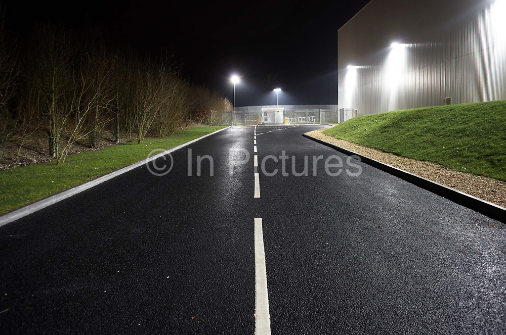 Seen from the middle of the road, an empty highway landscape is seen at night alongside a giant generic warehouse wall at the DIRFT warehouse logistics park in Daventry, Northamptonshire England. The tarmac is dark and the newly-painted white painted lines stand out. This 365 acre site off Junction 18 of the M1 motorway is a hub for road, rail and service infrastructure, some 2.3m sq.ft. of distribution and manufacturing floorspace had been constructed by 2004 and occupiers including Tesco's, Tibbett & Britten plc, Ingram Micro, Royal Mail, the W.H. Malcolm Group, Eddie Stobart Ltd, Wincanton and Exel, have been attracted to this unique logistics location.