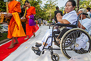 20 OCTOBER 2012 - BANGKOK, THAILAND:  A woman prays as Buddhist monks pass her at a special alms giving ceremony in Bangkok. More than 2,600 Buddhist Monks from across Bangkok and thousands of devout Thai Buddhists attended the mass alms giving ceremony in Benjasiri Park in Bangkok Saturday morning. The ceremony was to raise food and cash donations for Buddhist temples in Thailand's violence plagued southern provinces. Because of an ongoing long running insurgency by Muslim separatists many Buddhist monks in Pattani, Narathiwat and Yala, Thailand's three Muslim majority provinces, can't leave their temples without military escorts. Monks have been targeted by Muslim extremists because, in the view of the extremists, they represent the Thai state.       PHOTO BY JACK KURTZ
