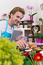 Mid adult man in flower shop checking goods with digital tablet, smiling