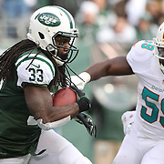Running back Chris Ivory, New York Jets, shakes off the challenge of Dannell Ellerbe, Miami Dolphins, in action during the New York Jets Vs Miami Dolphins  NFL American Football game at MetLife Stadium, East Rutherford, NJ, USA. 1st December 2013. Photo Tim Clayton