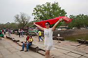 An Asian woman waves her red scarf in the air in the ancient grounds of Angkor Wat temple grounds Siem Reap, Cambodia. Angkor Wat is one of UNESCO's world heritage sites. It was built in the 12th century and covers 162 hectares.  It is Cambodia's main tourist attraction.